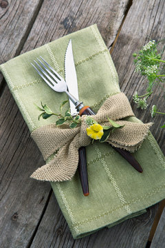 Burlap ribbon and herbs around napkin and silverware