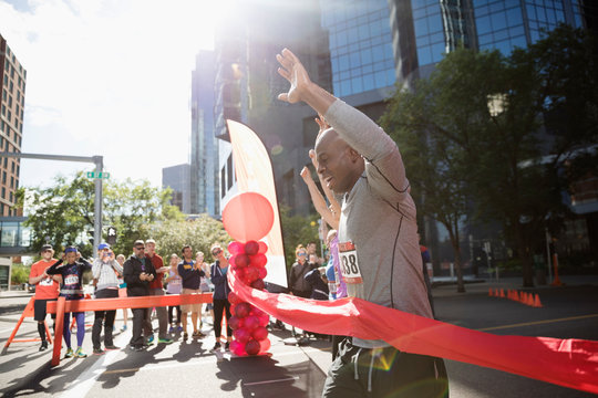 Exuberant male marathon runner crossing finish line with arms raised