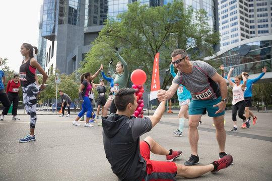 Male marathon runner helping tired runner at finish line