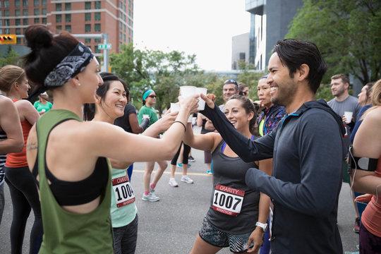 Marathon runners toasting water glasses on urban street