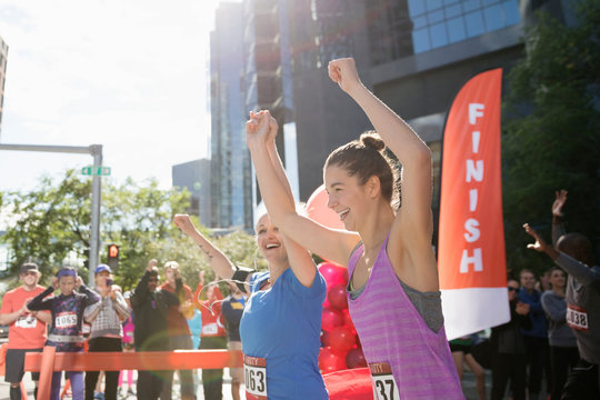 Exuberant female marathon runners holding hands crossing finish line with arms raised