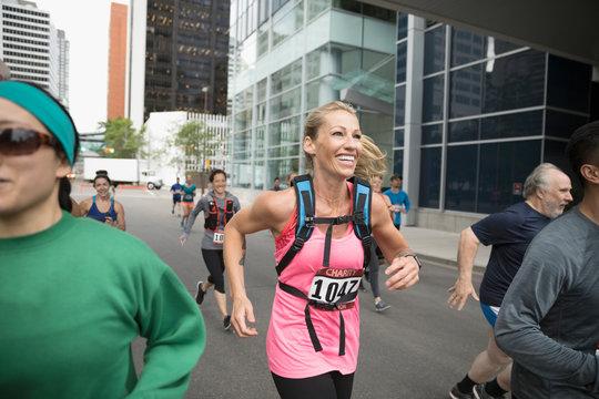 Smiling, enthusiastic female runner running on urban street