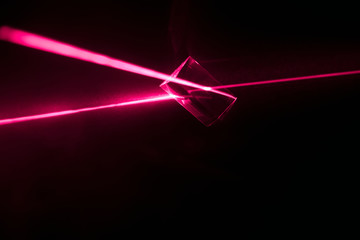 Creative abstract red laser prism refracting from cube