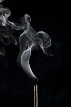 Extinguished matchstick smoke on black background