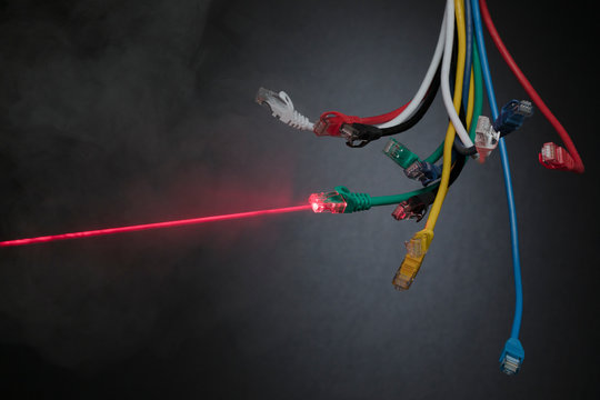 Red laser from contrasting multicolor computer cables dangling in bundle