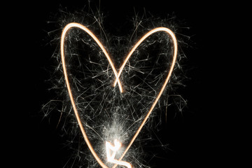 Creative, heart-shaped spark of love on black background
