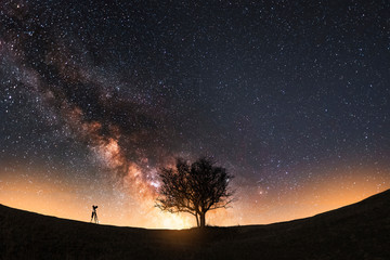 Foto op Aluminium Grijze traf. Night landscape. The camera on the tripod and tree silhouette on the hill under the bright beautiful milky way galaxy.