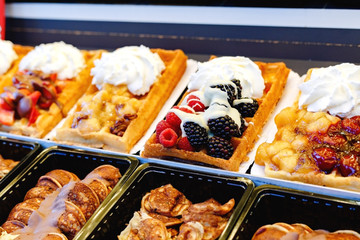 Belgian waffles street food with different toppings, fruits, sweets, whipped cream. Showcase pastry shop Belgian waffles of various types. Stock Photo Waffle desserts with berries, cream, chocolate.