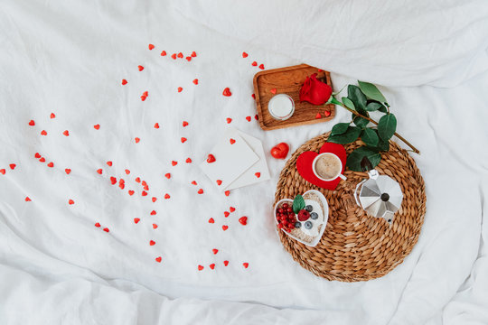 Valentines day breakfast with muesli, coffee and red rose on bed. Flat lay, top view, heart shape love concept valentines day