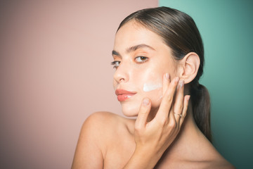 Sexy healthy woman applying cream or lotion with moisturizer to skin face. Perfect pure skin. Healthy and wellness concept. Natural beauty and no make up concept.