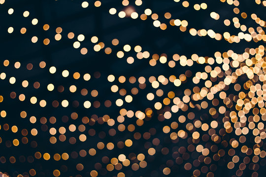Decorative outdoor string lights at night time, Defocused Background, night city life backdrop, party time with Yellow bokeh balls