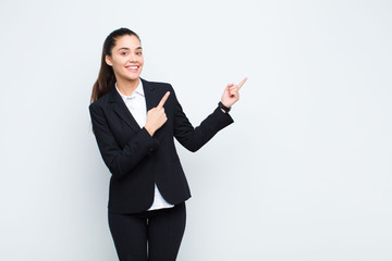 young pretty woman smiling happily and pointing to side and upwards with both hands showing object...