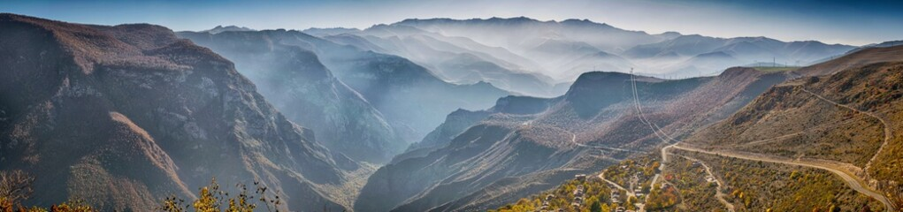 Beautiful panoramic view from the top of tatev gorge while the famous longest cable car Wings of Tatev and small village. South Armenian autumn landscape with Caucasus mountain range and foggy canyon