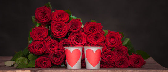 large bunch of red roses and two cups with hearts. Love concept, valentine day, wedding, date