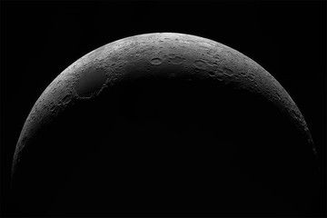Crescent of a young moon with a large increase. Moon, view through a telescope. The moon with craters. Real photos of space objects through a telescope.