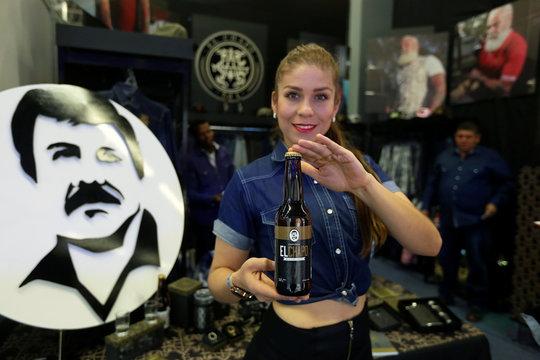 """A woman shows a bottle of """"El Chapo"""" beer at the Expo Guadalajara, in Guadalajara"""