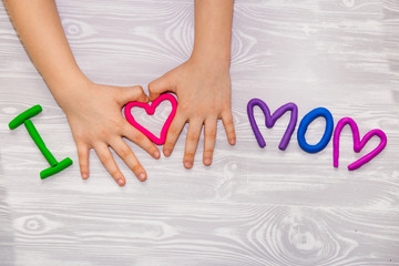 I love mom text from plasticine with kid hands on white wooden background. Happy mothers day. Fun kids handmade craft