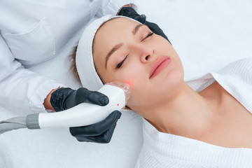 Young woman receiving laser treatment in cosmetology clinic