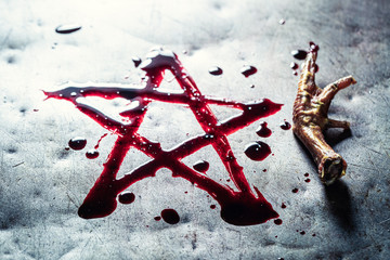 Pentagram drawn from blood on metal table with crow's paw