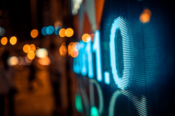 Financial stock exchange market display screen board on the street  with city scene reflect on glass.