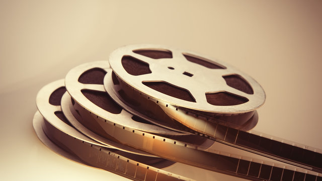 Stack of bobbins 16mm film strip on a light background. Cover.