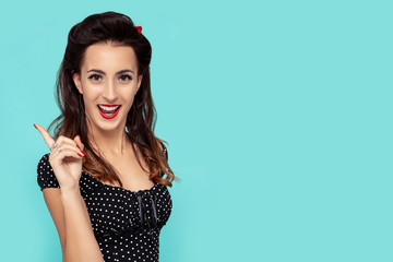 Pin-Up beautiful woman with an idea pose on turquoise background with copy space