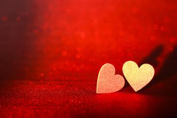 Due cuori scintillanti color oro su sfondo in glitter rosso