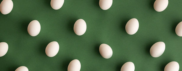 Flat lay of white naural organic eco hen eggs organized on dark olive green background in pattern
