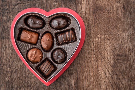 Simple heart shaped box of chocolate Valentine's Day candy on a wood table
