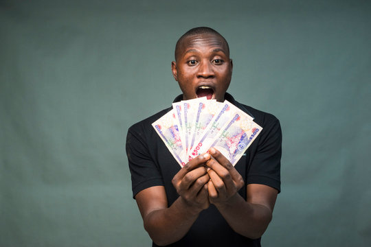 young black man holding some cash, feeling surprised and happy