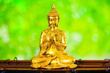 金の仏像と爽やかな緑背景