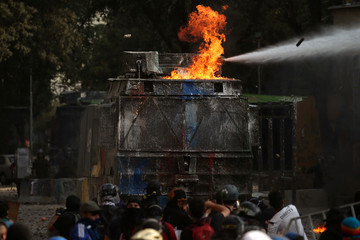 A riot police water truck is hit by a molotov bomb during anti-government protests in Santiago