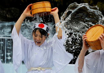 Women splash themselves with cold water during the annual cold water endurance ceremony, to purify their souls and wish for good fortune in the new year, at the Kanda Myojin shrine in Tokyo