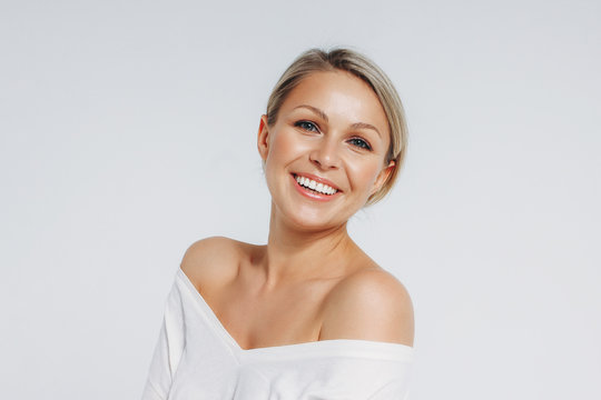 Beauty portrait of blonde smiling laughing woman 35 year plus clean fresh face isolated on white background