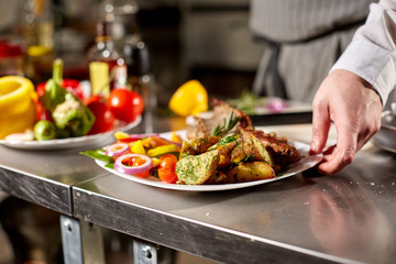 the chef prepares in the restaurant. Grilled rack of lamb with fried potatoes and fresh vegetables