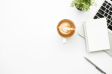 Wall Mural - White minimalist office desk table with blank notebook page with pen, cup of latte coffee and laptop computer. Top view with copy space, flat lay.