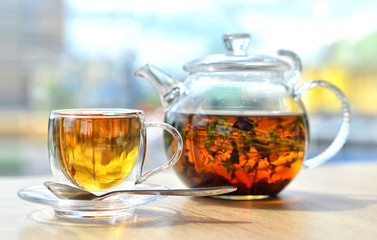 Foto op Plexiglas Thee A glass teapot with tea and a glass cup with tea stand on the table ON A LIGHT BACKGROUND