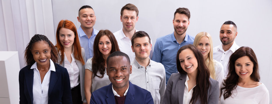 Group Of Smiling Businesspeople Standing In Office