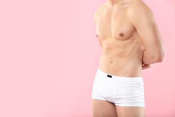 Handsome man in underwear on color background