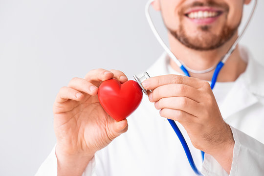 Male cardiologist with red heart on light background, closeup