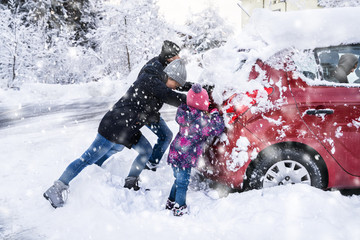 Family Pushing A Car Stuck In The Snow