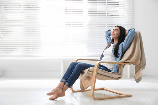 Young woman relaxing in armchair near window at home