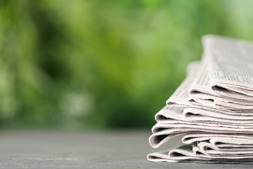 Stack of newspapers on grey table against blurred green background, space for text. Journalist's work