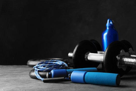 Gym equipment and accessories on stone floor against dark background