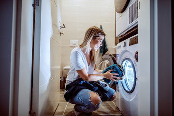 Smiling caucasian blond worthy housewife dressed casual crouching in bathroom and loading washing machine with dirty clothes in late hours.