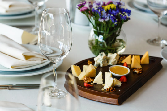 Wine and cheese concept, cheeseboard in a restaurant, variety of cheese and sauce, empty wineglass. Cheese tasting, banquet party, celebration