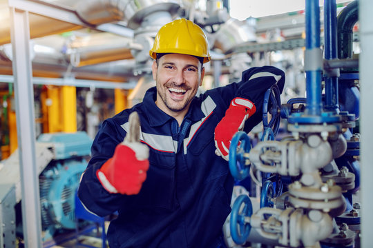 Smiling handsome caucasian worker in protective working clothes and with helmet on head leaning on boiler and giving thumbs up while standing in factory.
