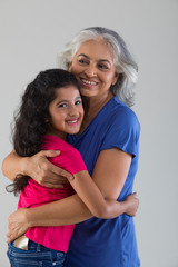 Portrait of a happy grandmother hugging her grand-daughter.