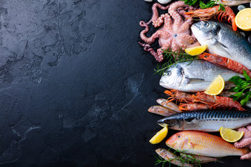 Fresh raw fish and seafood assortment on black slate background. Top view. Copy space.