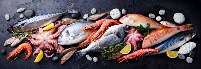 Aluminium Prints Food Fresh fish and seafood assortment on black slate background. Top view.
